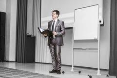 Högtalaren rymmer en presentation av ett nytt finansiellt projekt som framme står av ett tomt advertizingbräde i modernt arkivbilder