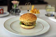 Högvärdig hamburgare med ostgrönsallat och utsökt mål för tomat, unik kokkonst för lyxigt kött i storgubbegastronomirestaurang Arkivfoton