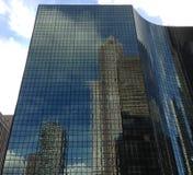Högväxt byggnad som reflekterar andra byggnader Arkivfoton