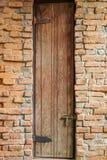 Högväxt dörr på tegelstenväggen arkivbild