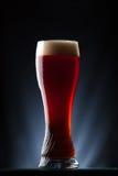 Högväxt exponeringsglas av mörkt öl över en mörk bakgrund Arkivfoto
