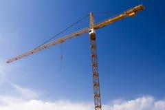 Högväxt konstruktionskran mot blå himmel royaltyfri bild