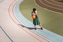 Högväxt magert kvinnaanseende med den orange bollen på stadion royaltyfri bild