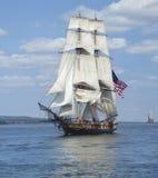 Högväxt skepp med amerikanska flaggansegling på blått vatten Arkivbild