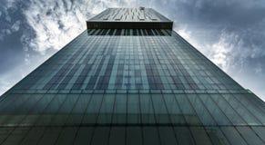 Högväxt stads- skyskrapa i finansiellt område med lynniga dramatiska moln royaltyfri fotografi