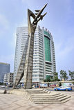 Högväxt staty med kontorsbyggnad på bakgrund, Yantai, Kina Arkivfoton