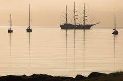 högväxt vatten för lugna shipsilhouette Arkivbilder
