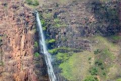 Högväxt vattenfall som applåderar ner en stenig klippa i tropiskt landskap i Hawaii Arkivfoto