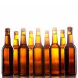 Högväxta ölflaskor med inga etiketter och metalllock Arkivbild