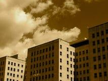 Högväxta byggnader mot en molnig himmel i Sepia Royaltyfria Foton
