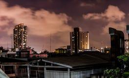 Högväxta byggnader på natten, orange himmel Fotografering för Bildbyråer