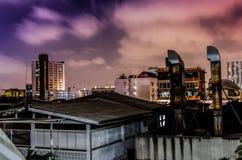 Högväxta byggnader på natten, orange himmel Arkivfoton