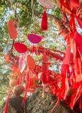 Högväxta träd dekoreras fullständigt med röda band många röda band som binds till träd askfat royaltyfri bild