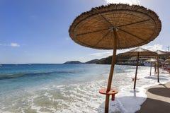 Högvatten på stranden med den behandlade slags solskydd Arkivbild