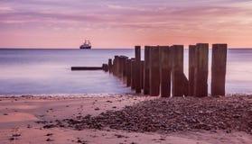 Högvatten som rullar över sandvågbrytare Fotografering för Bildbyråer