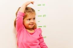 Höhenmessung durch kleines Mädchen an der Wand Lizenzfreies Stockbild