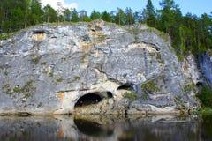 Höhle im Felsen nahe Fluss stockbild