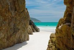 Höhlen Sie in den Felsen in einem kristallenen freien Meer aus Stockfotos