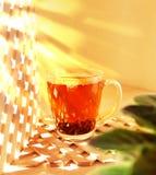 Höhlen Sie Glas schwarzen Tee auf einem hölzernen Hintergrund Morgen, sonniges Lizenzfreies Stockfoto