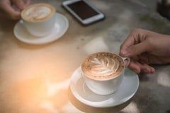 Höhlen Sie Kaffee und Telefon auf dem Tisch in der Kaffeestube am Morgen Stockbild
