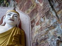 Höhlen Sie Wand mit Miniatur-Buddhas und Statue im Vordergrund, Birma aus Stockfotografie