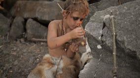 Höhlenbewohner, männlicher Junge, der ursprüngliche Steinwaffe im Lager herstellt stock video