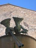 Höjdpunkt av en springbrunn med statyer av två barn med stora hattar som lutar ut med bak en forntida kyrka till Foligno, Italien Arkivbilder