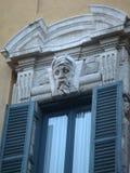 Höjdpunkt av ett fönster med huvudet av en staty av en äldre man i den historiska mitten i Rome Italia Royaltyfri Foto