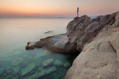 Höjdpunkt för soluppgång för ensamhetflicka hållande ögonen på upp på klippan vid havet Arkivfoto