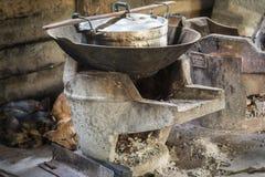 Hölzerne Öfen oder Holzkohlengrills und -töpfe in der Küche von Leuten Stockbild