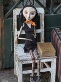 Hölzerne abgedroschene Frauen-Marionette auf weißem Stuhl Stockbilder