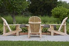 Hölzerne Adirondack-Stühle, die auf ein Picknick warten Stockbild