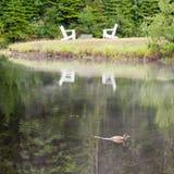 Hölzerne adirondack Stühle durch den See Stockfoto
