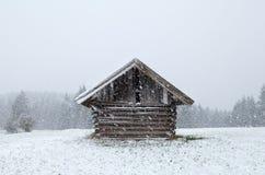 Hölzerne alte Hütte an den Schneefällen Lizenzfreie Stockfotos