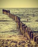Hölzerne Anhäufungen auf Strand, Weinlese Retro- instagram Effekt stockfoto