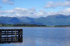 Hölzerne Anlegestelle in den See mit Gebirgszughintergrund Stockfotos