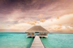 Hölzerne Anlegestelle, die zu Entspannungshäuschen führt Malediven-Inseln bei Sonnenaufgang lizenzfreie stockbilder