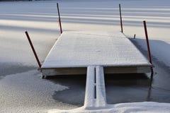 Hölzerne Anlegestelle in einem gefrorenen See Stockbild
