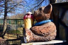 Hölzerne Bärnpuppe, die Eiscreme im Park isst stockfoto