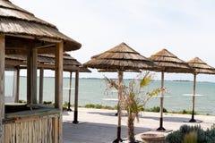 Hölzerne Bambushütte als Barstrohdach auf Strand und viel Strohsonnenschirm im Panoramablick lizenzfreie stockfotografie