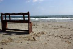 Hölzerne Bank auf dem Strand Stockbild