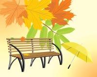 Hölzerne Bank und Regenschirm auf dem Herbsthintergrund Stockfotos