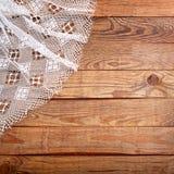 Hölzerne Beschaffenheit, Holztisch mit Draufsicht der weißen Spitzetischdecke Lizenzfreie Stockfotografie