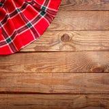 Hölzerne Beschaffenheit, Holztisch mit Draufsicht des roten Tischdeckenschottenstoffs Lizenzfreie Stockfotos