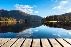 Hölzerne Beschaffenheit und schöner Autumn Landscape Background mit bunten Bäumen, Bergen, Wolken im blauen Himmel und See-Reflex lizenzfreie stockfotografie
