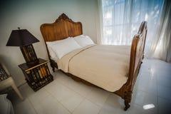 Hölzerne Bettmöbel des klassischen Teakholzes im warmen und gemütlichen Schlafzimmer, Ne Lizenzfreie Stockbilder