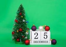 Hölzerne Blöcke mit Datum am 25. Dezember nahe bei Weihnachtsbaum Lizenzfreie Stockfotos