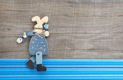 Hölzerne blaue Kaninchendekoration auf grauem hölzernem Hintergrund mit Blauem Lizenzfreie Stockbilder