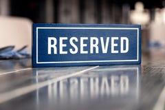 Hölzerne blaue weiße rechteckige Platte der Nahaufnahme mit der reservierten Stellung des Wortes auf grauer Tabelle im Restaurant lizenzfreie stockfotografie