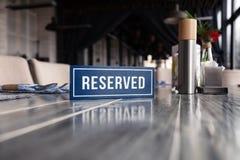 Hölzerne blaue weiße rechteckige Platte der Nahaufnahme mit der reservierten Stellung des Wortes auf grauer Weinlesetabelle im Re stockbild